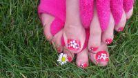 Blümchen mit Strass auf pinkfarbenen Fußnägeln Füsse