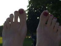Lila Nagellack Füße im Park Füsse