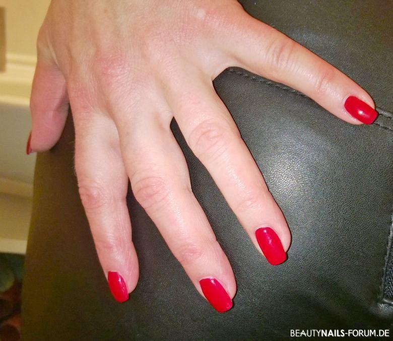 orange rote Fingernägel auf Lackhose